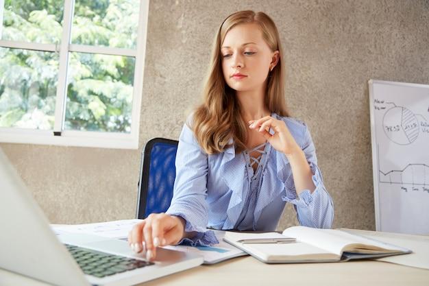Blondynka bizneswoman pracuje przy biurowym biurkiem