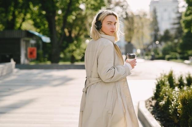 Blondynka chodzi w lecie miasta z filiżanką kawy