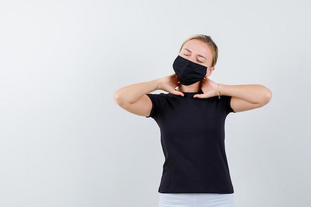 Blondynka cierpiąca na bóle karku w czarnej koszulce, czarnej masce i wyglądająca na bolesną