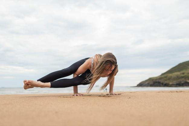 Blondynka co joga. jest na plaży podczas pochmurnego zachodu lub wschodu słońca. ona jest sama. ma na sobie odzież sportową. jest kaukaską dziewczyną z niemiec