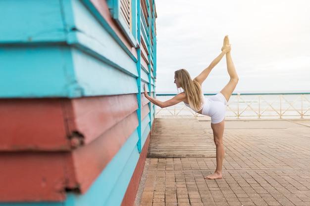 Blondynka co joga z białą odzież sportową. obsługiwany w niebiesko-czerwonej drewnianej kabinie na plaży