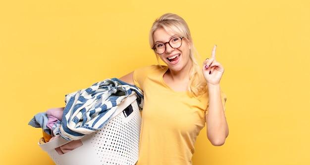 Blondynka czując się jak szczęśliwy i podekscytowany geniusz po zrealizowaniu pomysłu, radośnie podnosząc palec, eureka!