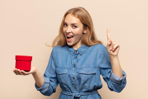 Blondynka czuje się jak szczęśliwa i podekscytowana geniusz po zrealizowaniu pomysłu, radośnie podnosząca palec, eureka!