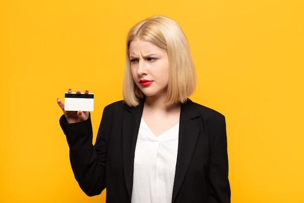 Blondynka czuje się smutna, zdenerwowana lub zła i patrzy w bok z negatywnym nastawieniem, marszczy brwi w niezgodzie