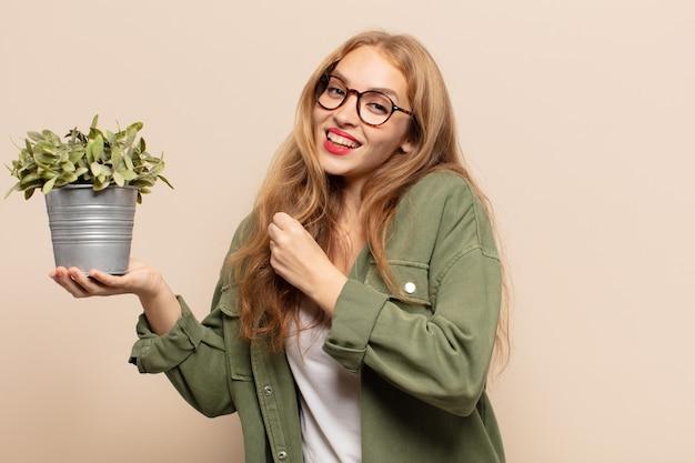 Blondynka czuje się szczęśliwa, pozytywna i odnosząca sukcesy, trzymając roślinę