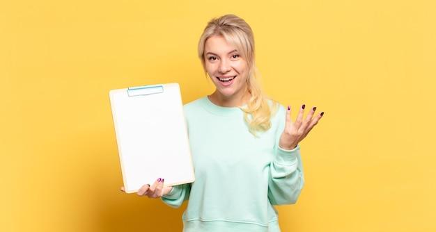 Blondynka czuje się szczęśliwa, zaskoczona i pogodna, uśmiechnięta z pozytywnym nastawieniem, realizująca rozwiązanie lub pomysł