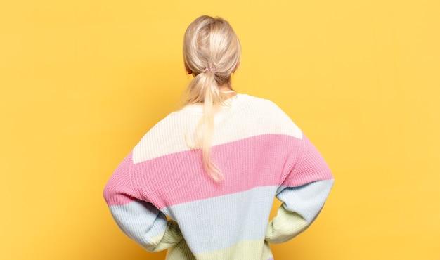 Blondynka czuje się zagubiona lub pełna lub ma wątpliwości i pytania, zastanawia się, z rękami na biodrach, widok z tyłu