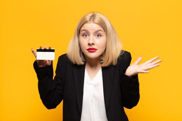 Blondynka czuje się zakłopotana i zdezorientowana, wątpi, waży lub wybiera różne opcje ze śmiesznym wyrazem twarzy