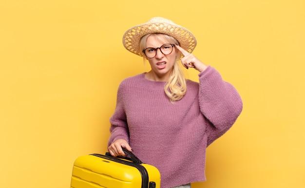 Blondynka czuje się zdezorientowana i zdziwiona, pokazując, że jesteś szalony, szalony lub oszalały