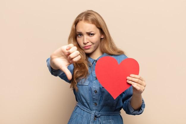 Blondynka czuje się zła, zła, zirytowana, rozczarowana lub niezadowolona, pokazuje kciuki w dół z poważnym spojrzeniem