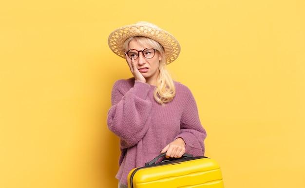 Blondynka czuje się znudzona, sfrustrowana i senna po męczącym, nudnym i żmudnym zadaniu, trzymając twarz ręką