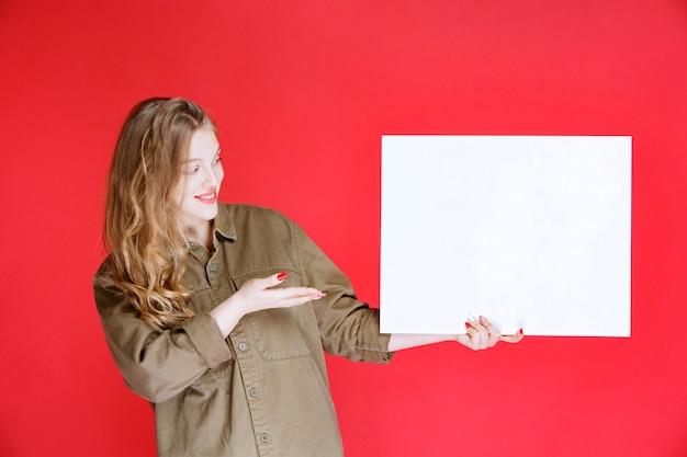 Blondynka demonstruje dzieło sztuki na płótnie.