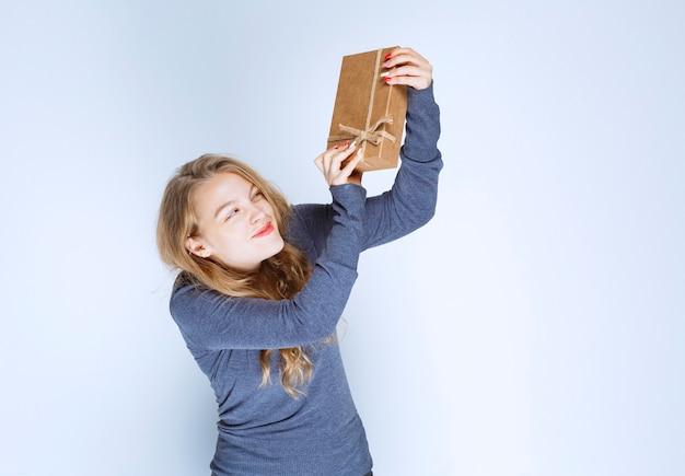 Blondynka demonstruje swoje pudełko kartonowe i czuje się pozytywnie.
