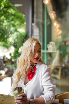 Blondynka długie włosy trzyma czekoladowego słodka bułeczka w caf�