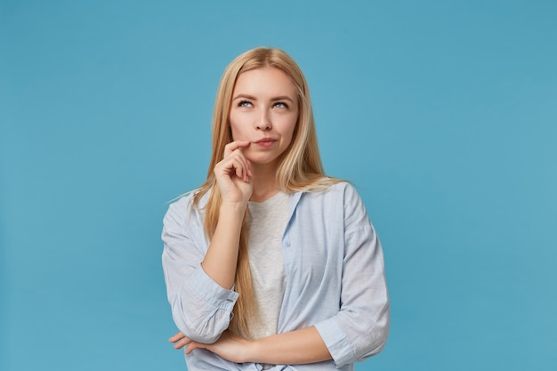 Blondynka długowłosa stojąca, patrząc w zamyśleniu w górę i wydrążająca usta, ubrana w zwykłe ubranie i trzymająca rękę na brodzie