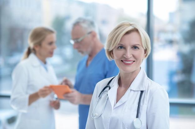 Blondynka dojrzała kobieta lekarz uśmiechając się do kamery, jej koledzy stojąc z tabletem za