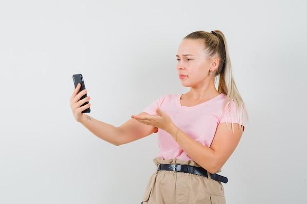 Blondynka dyskutuje coś na czacie wideo w koszulce, spodniach i wygląda na zdezorientowanego, widok z przodu.