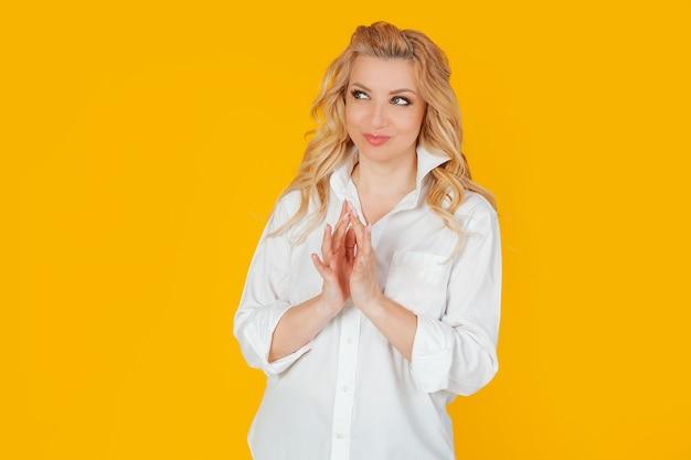 Blondynka europejka w białej koszuli, jakby robiąca plan, uśmiechnięta tajemniczo, spoglądająca w bok, chcąca zrobić coś nielegalnego lub potajemnie.