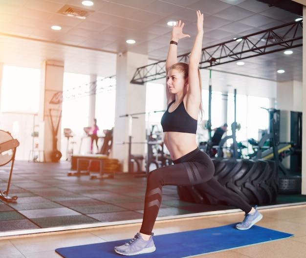 Blondynka fitness robi rzuca nogi z podniesionymi rękami na siłowni