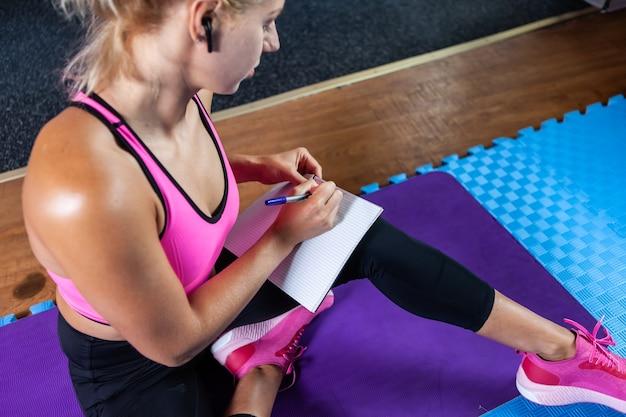Blondynka fitness zastanawia się i pisze w zeszycie treningowym plan treningu, siedząc na macie w klasie fitness.
