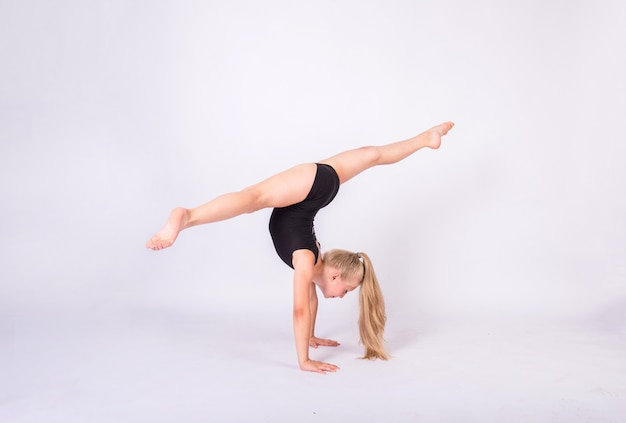 Blondynka gimnastyczka w czarnym stroju kąpielowym rozłupuje ręce na białej ścianie