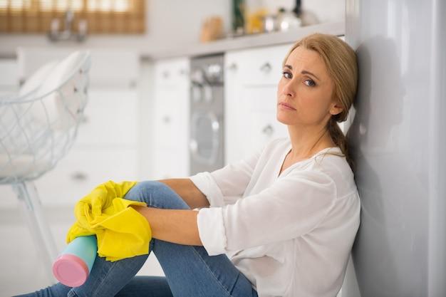 Blondynka gospodyni w ochronnych rękawiczkach czuje się zmęczona