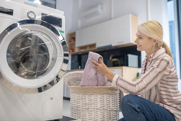 Blondynka gospodyni wkłada ubrania do pralki