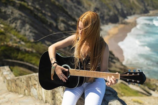 Blondynka gra na gitarze akustycznej. ona siedzi na klifie na wybrzeżu w słoneczny dzień
