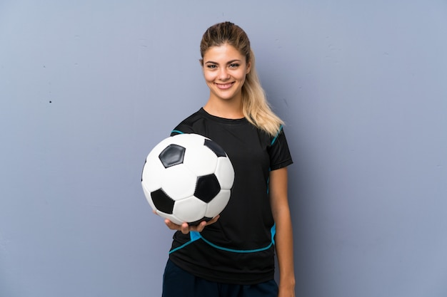 Blondynka gracza futbolu nastolatka dziewczyna nad szarości ścianą