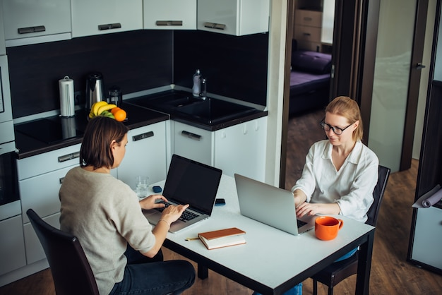Blondynka i brunetka pracują na laptopach, siedząc naprzeciw siebie przy stole w kuchni. coworking w przytulnym domowym wnętrzu.