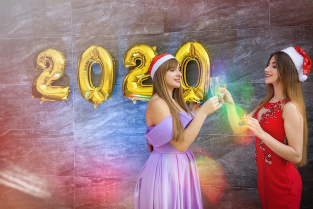 Blondynka i brunetka w eleganckich sukniach wieczorowych pozują z kieliszkami do szampana