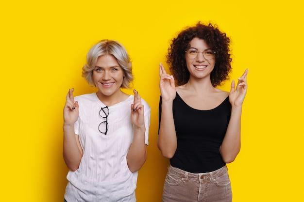 Blondynka i jej kędzierzawy przyjaciel uśmiechają się ślicznie krzyżując palce na żółtej ścianie