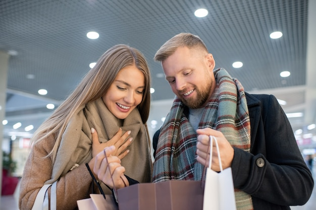 Blondynka i młody mężczyzna, patrząc na zakup w jednej z papierowych toreb, omawiają cenę po udanych zakupach
