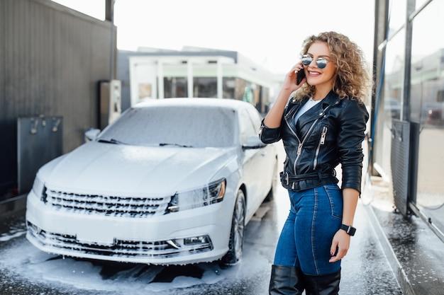 Blondynka i odnosząca sukcesy kobieta biznesu rozmawiają przez telefon w pobliżu jej samochodu na myjni samochodowej