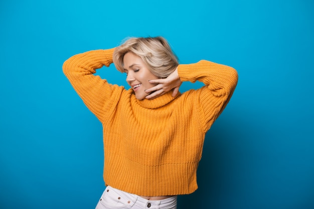 Blondynka kaukaski kobieta w żółtym swetrze z dzianiny, gestykuluje przyjemność na ścianie w niebieskim studio