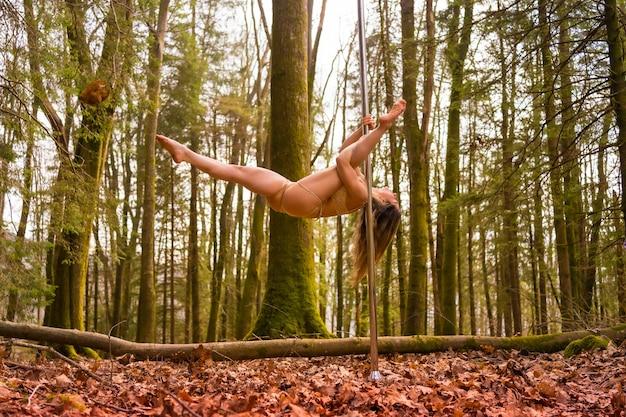 Blondynka kaukaski taniec taniec na rurze w lesie. wyczyny kaskaderskie na łonie natury z przenośnym kijem