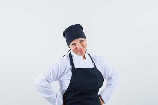 Blondynka kładzie ręce na talii i pozuje z przodu w czarnym mundurze kucharza i wygląda ładnie.