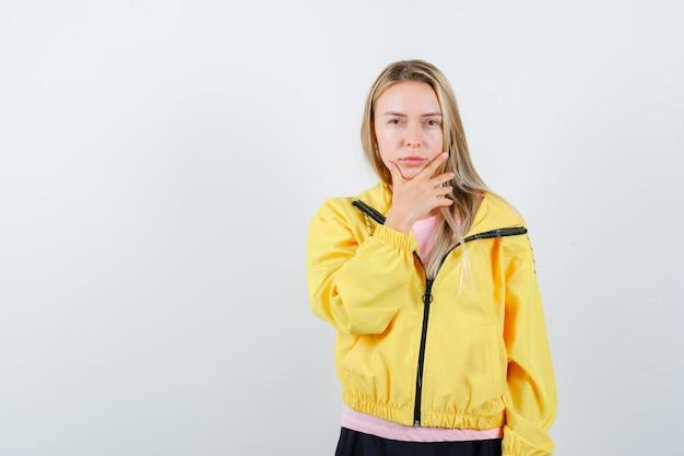 Blondynka kładzie rękę na brodzie w różowej koszulce i żółtej kurtce i wygląda poważnie