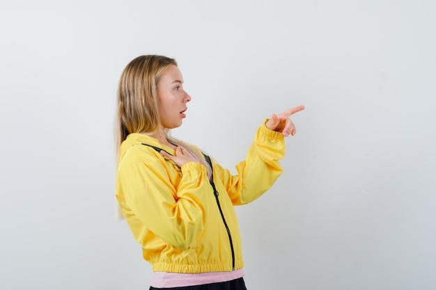 Blondynka kładzie rękę na klatce piersiowej, wskazując w prawo w różowy t-shirt i żółtą kurtkę i patrząc na zdziwioną.