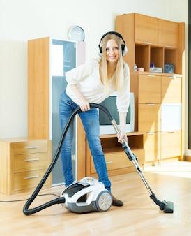 Blondynka kobieta w czyszczeniu hełmofon z odkurzaczem