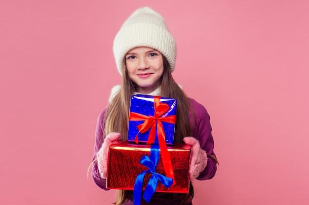 Blondynka kręcone fryzury nastolatek dziewczyna w różowy kapelusz z dzianiny, szalik i rękawiczki góra prezentów boże narodzenie pudełko różowym tle studio. noworoczny prezent w rękach dziecka płci żeńskiej, która ma życzenie copyspace