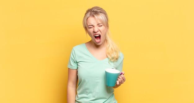 Blondynka krzyczy agresywnie, wygląda na bardzo wściekłą, sfrustrowaną, oburzoną lub zirytowaną, krzycząc nie