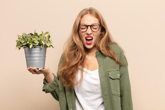 Blondynka krzyczy agresywnie, wygląda na bardzo złą, sfrustrowaną, oburzoną lub zirytowaną, krzyczącą nie