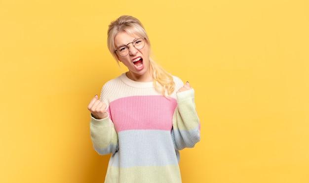 Blondynka krzyczy agresywnie z gniewnym wyrazem twarzy lub z zaciśniętymi pięściami świętując sukces