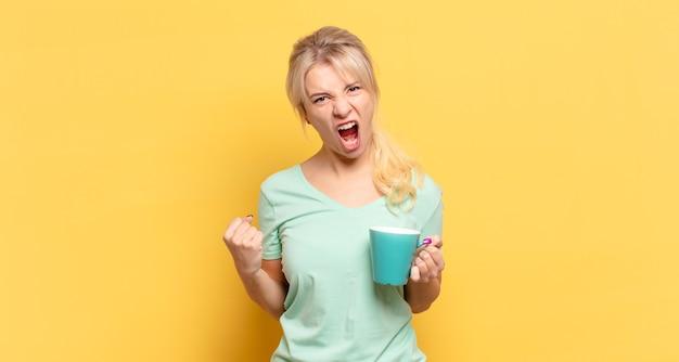 Blondynka krzyczy agresywnie z gniewnym wyrazem twarzy lub z zaciśniętymi pięściami świętuje sukces