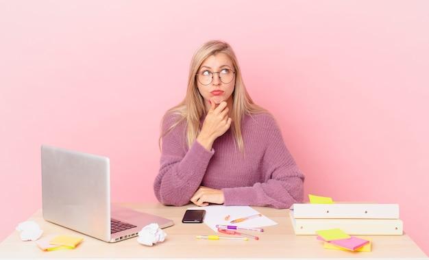 Blondynka, ładna kobieta, młoda blond kobieta myśli, wątpi, jest zdezorientowana i pracuje z laptopem