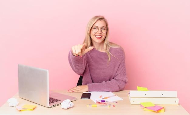 Blondynka, ładna kobieta, młoda blond kobieta, wskazując na kamerę, wybierającą cię i pracująca z laptopem