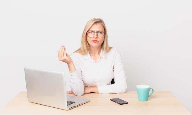 Blondynka ładna kobieta młoda blondynka robi gest kaprysu lub pieniędzy, mówiący ci, aby zapłacić i pracować z laptopem