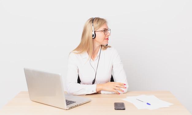 Blondynka, ładna kobieta, młoda blondynka z widokiem z profilu, myśląca, wyobrażająca sobie lub marząca na jawie i pracująca z laptopem