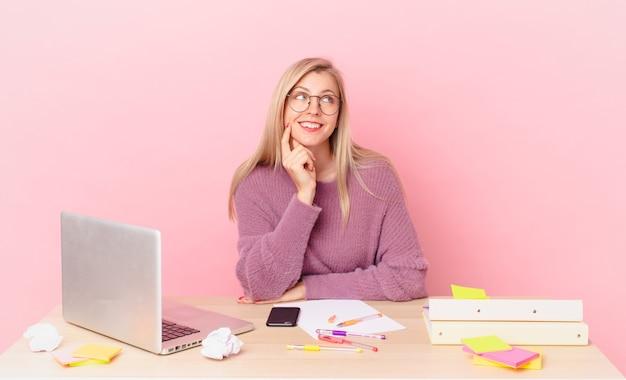 Blondynka ładna młoda blond kobieta uśmiecha się radośnie i marzy lub wątpi i pracuje z laptopem